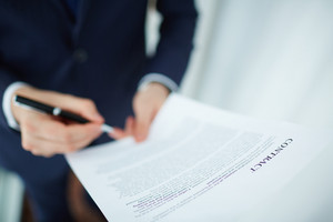 Image Of Contract Being Read And Signed By Businessman
