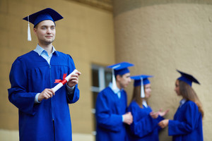 Friendly Students In Graduation Gowns Interacting With Pensive Guy In Front