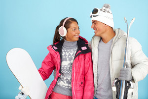 Portrait Of Pretty Girl And Handsome Man In Winterwear Holding Snowboard And Skis