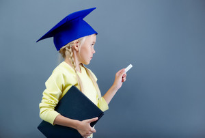 Portrait Of Lovely Girl In Graduation Hat Writing With Chalk