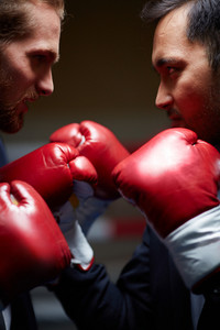 Dissatisfied Businessmen In Boxing Gloves Looking At One Another