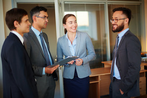 Group Of Happy Colleagues Looking At Their Partner While Interacting In Office
