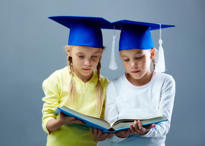 Portrait Of Lovely Twin Girls In Hats With Tassels Reading Book