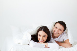 Portrait Of Joyful Young Couple Lying In Bed And Laughing