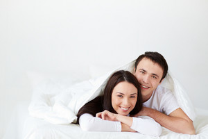 Portrait Of Joyful Young Couple Lying In Bed And Looking At Camera