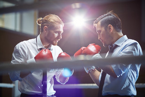 Serious Businessmen In Boxing Gloves Attacking One Another In Gym Or Boxing Ring