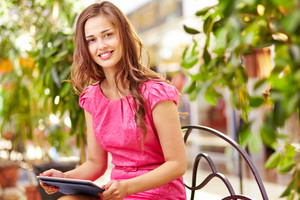 Adorable Girl With Touchpad Sitting In The Mall And Looking At Camera
