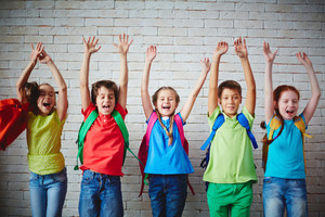 Several Ecstatic Classmates With Backpacks Raising Arms Against Brick Wall