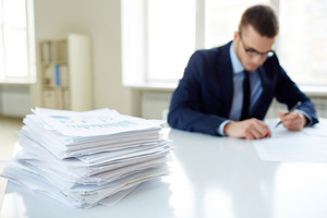Stack Of Documents On The Desk And Male Employee Working On Background