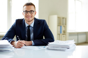 Portrait Of Smiling Employee Looking At Camera While Working