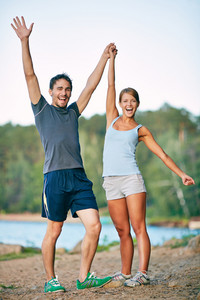 Photo Of Happy Couple Raising Arms Outdoors