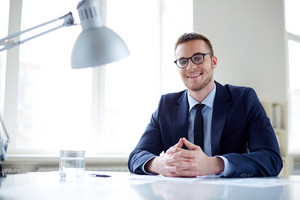 Portrait Of Smiling Employee Looking At Camera In Office