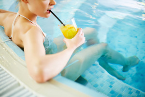 Yong Woman Sitting In Pool And Drinking Lemonade