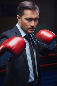Aggressive Asian Businessman In Red Boxing Gloves And Suit Looking At Camera
