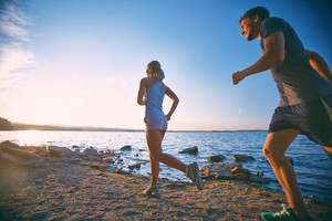 Photo Of Young Couple Running On The Coastline In The Morning