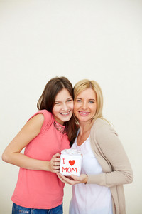 Teenage Girl And Her Mom With Small Present Looking At Camera And Smiling