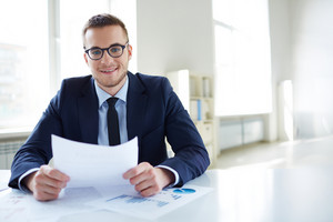 Portrait Of Smiling Employee With Paper Looking At Camera In Office