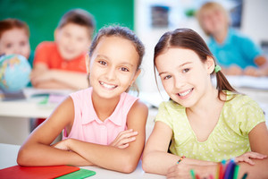 Cute Girls Looking At Camera At Lesson On Background Of Their Classmates