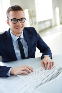 Portrait Of Smiling Employee With Laptop Looking At Camera In Office