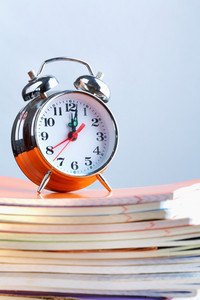 Stack Of Copybooks With Alarm Clock On Its Top
