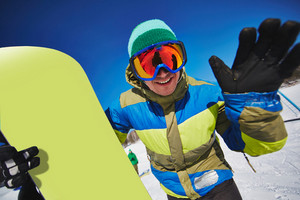 Young Sportsman With Snowboard Looking Through Eyeglasses At Winter Resort