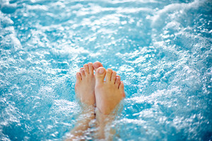 Close-up Of Female Legs In Hot Tub