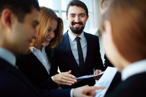 Group Of Business Partners Discussing Papers And Explaining Ideas At Meeting With Focus On Happy Man Looking At Camera