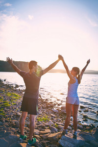 Photo Of Young Sporty Dates Standing On The Coastline With Raised Arms And Looking At One Another