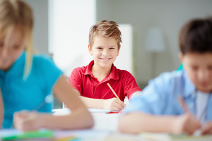 Portrait Of Cute Schoolboy Looking At Camera At Drawing Lesson