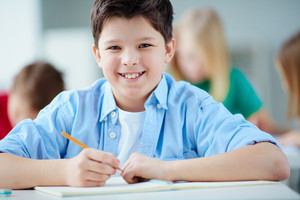 Portrait Of Happy Schoolboy At Workplace Looking At Camera With His Classmates On Background