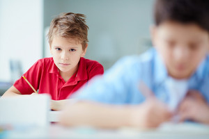 Portrait Of Serious Schoolboy Looking At Camera While Drawing At Lesson
