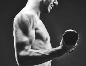 Close-up Of Young Guy With Bare Torso Doing Exercise With Barbell