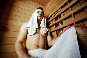 Good looking and attractive young man with muscular body relaxing in sauna hot