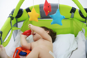 Happy baby sitting on bed playing with toys