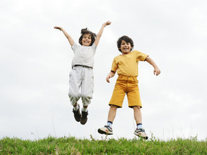 Child jumping on a green meadow