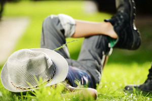 Relaxed child resting on summer park grass meadow