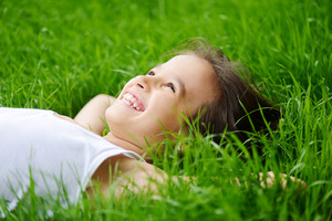 Happy little boy enjoying on grass field and dreaming