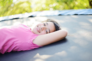 Portrait of a smiling little girl lying on trampoline