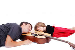 Happy father and daughter lie on guitar