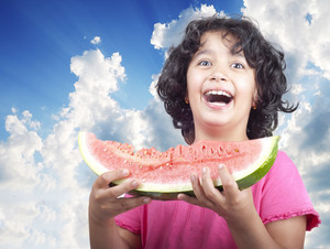 Caucasian girl offers a watermelon