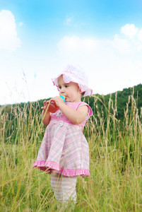 Baby girl standing in nature and drinking milk from bottle
