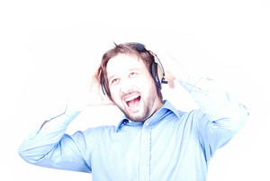 Young man with headphones on head smiling and shouting