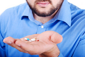 Man's palm with medicine pills on