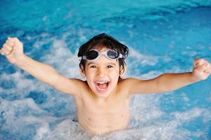 Super happy boy inside the swimming pool
