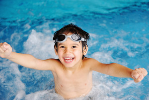 Little cute  boy in blue water of the swimming pool