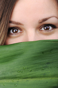 Closeup portrait of young beautiful woman with green leaf as copy space