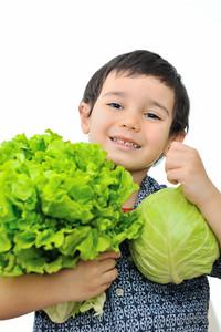 Cute little kid holding vegetables