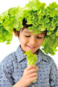 Kid with salad on his head as hat eating salad
