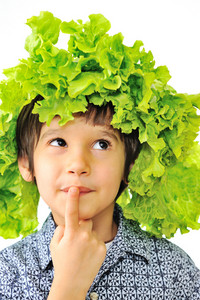 Curious little kid with salad on his head as hat