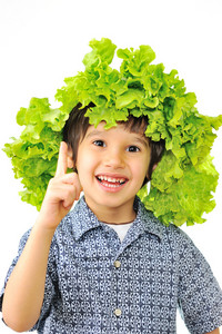 Kid with salad on his head as hat having an idea